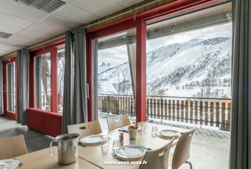 La salle à manger du centre de vacances Anaé offre une belle vue sur les montagnes enneigées