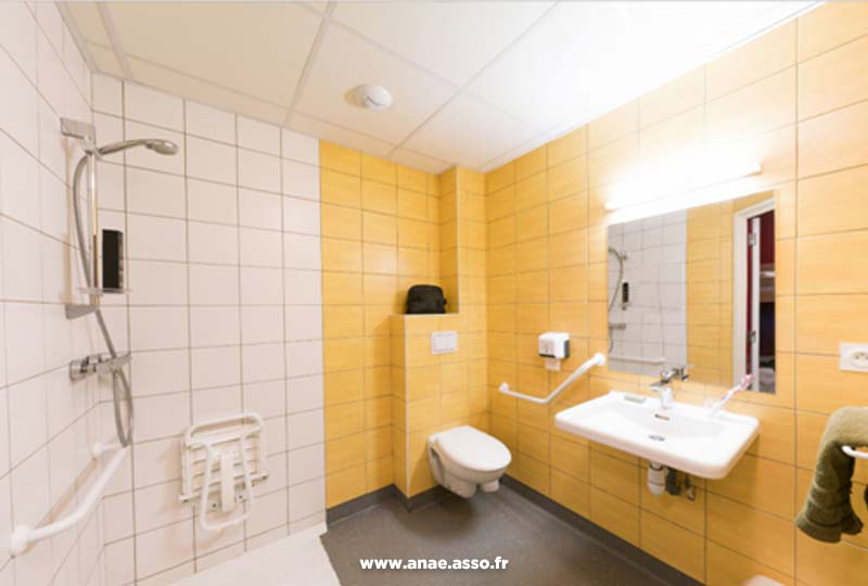 Exemple de salle-de-bain adaptée aux personnes à mobilité réduite avec barres de maintien et douche italienne